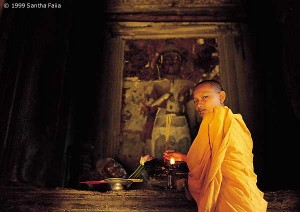 A Buddhist monk burns incense in the central sanctuary of Angkor Wat - still a place of living religion to this day.