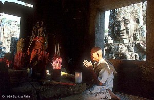 A Buddhist monk, overlooked by one of the 216 stone faces of Lokesvara, offers prayers in an inner shrine of the Bayon.