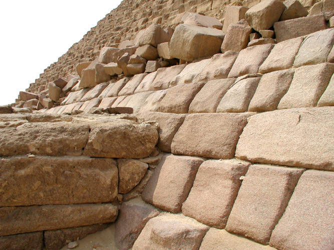 The casing stones on Menkaure's Pyramid were never finished. The photo shows the East face of the Pyramid with roughly finished casing stones. Source: Egyptarchive.co.uk