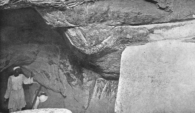 'Al Mamoun's Cavity', as viewed from the First Ascending Passage of the Great Pyramid, showing the upper butt-end of the granite plug to the right, and Judah standing at the inner end of the long passage, which was forced inward from the north side of the Pyramid by Caliph Al Mamoun in 820 A.D.